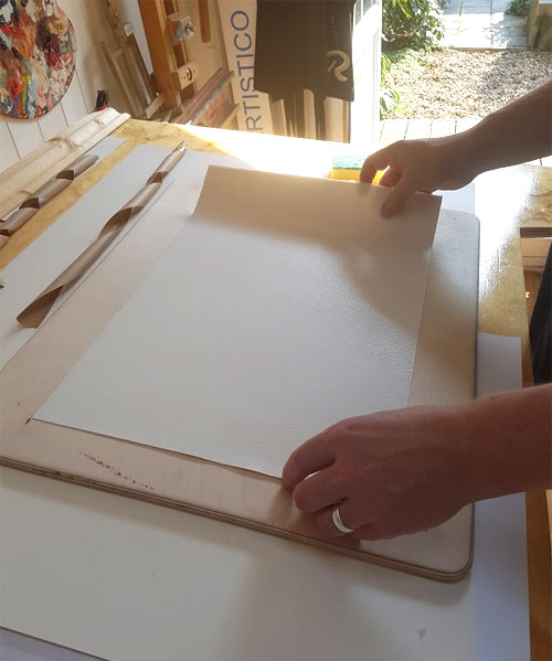 Laying the wet paper onto a suitable board